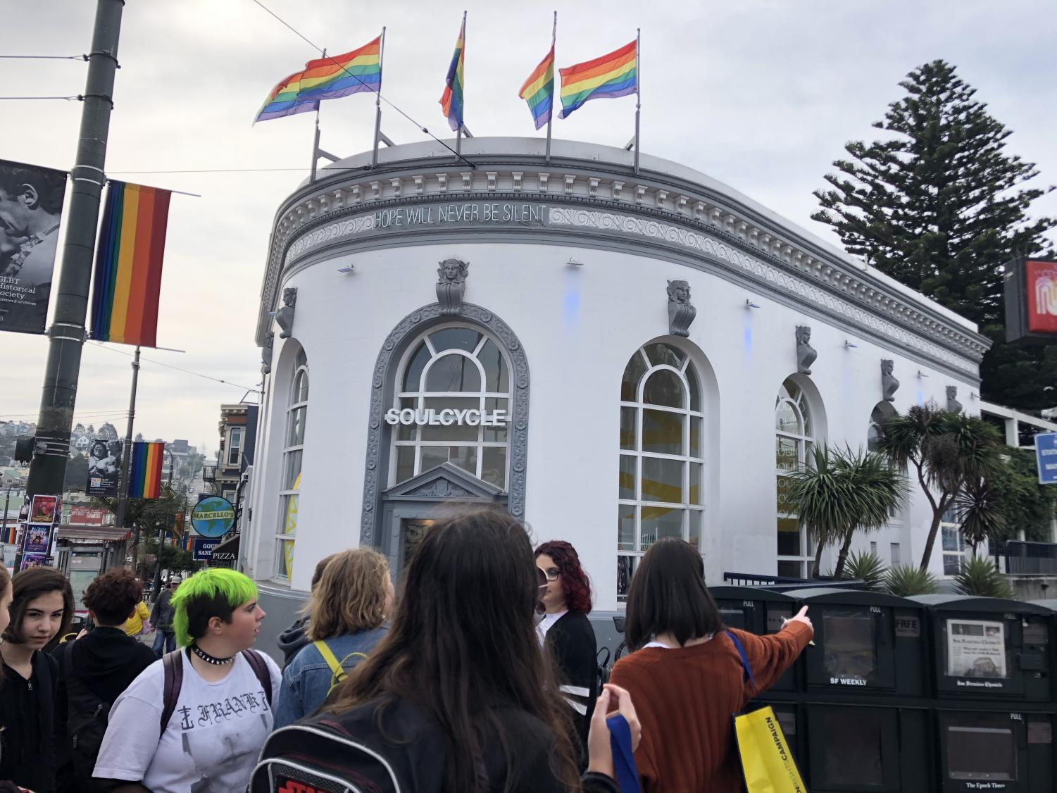 The GSA stops to admire a large rainbow flag before visiting Harvey Milk Plaza.