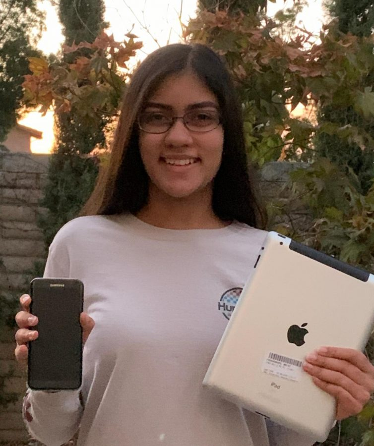 Tanya Bakshi ('23) smiles, holding some of the many devices she has donated to help seniors.