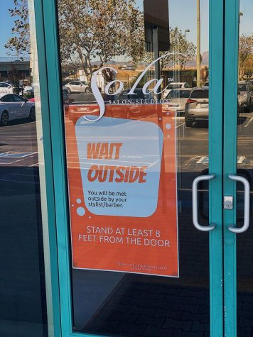 The front doors at Sola Salon Studios in Pleasanton are filled with signs to encourage social distancing to their best ability.