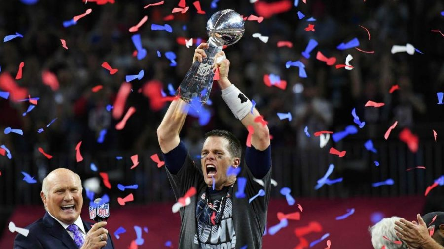 Here Brady holds one of his many Super Bowl trophies for the New England Patriots.