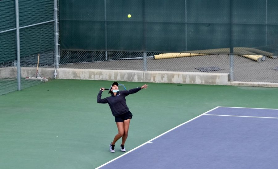 Knowing that focusing on the ball is key to tennis, Kruthika Gowda ('22) serves an overhand with her concentration solely on the yellow object.