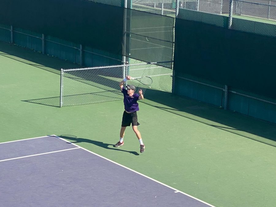 Brett Miller (21) jumps in happiness as he wins his point in his singles match.