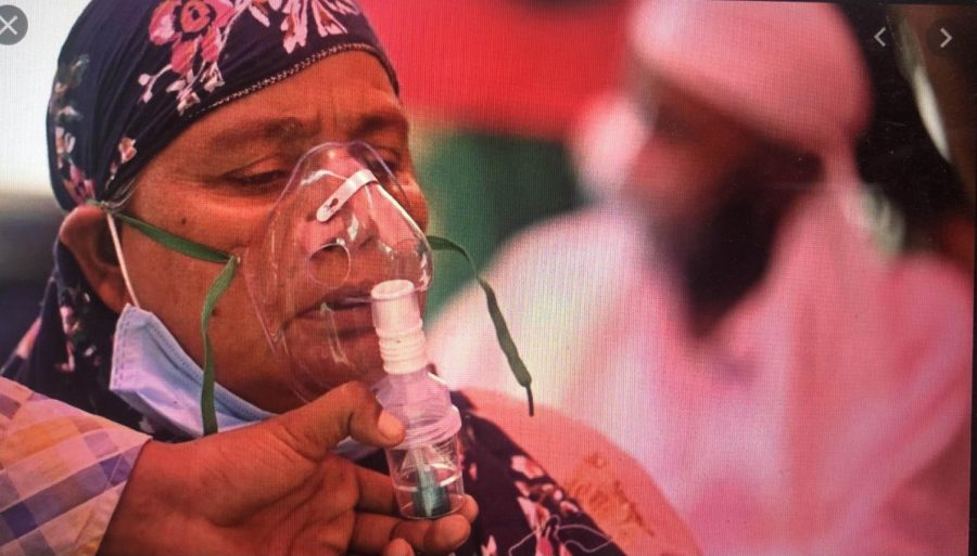 A woman is given oxygen, as she struggles to breathe due to the effects of Covid. Originally posted: BBC News.
