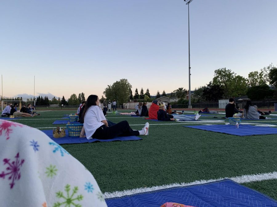 The picnic blankets are spread out across the football field and students are careful to wear masks while watching the movie Ferris Bueller's Day Off.