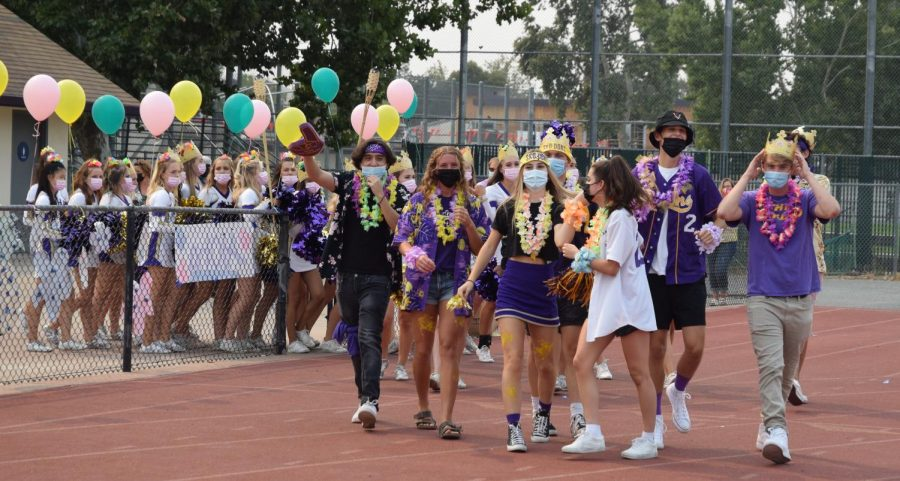 The Varsity Cheer team and the spirit team walk to the stands after welcoming students to the 2021-2022 Aloha Rally.