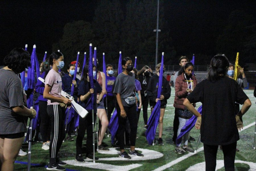 The colorguard meet with the captains to reflect on show performance and listen to announcments.
