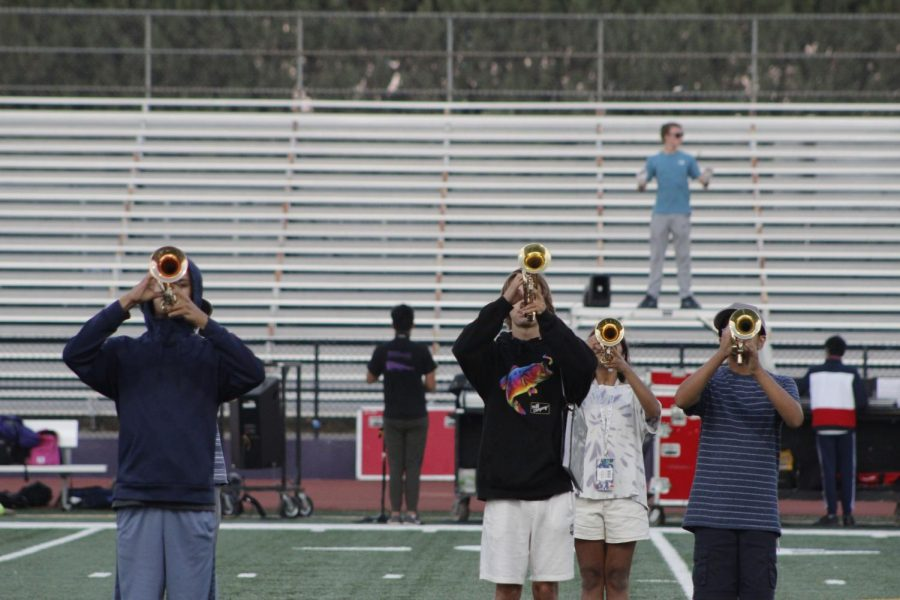 Trumpets performing with drum major in the background, making sure theyre in their perfect spots.