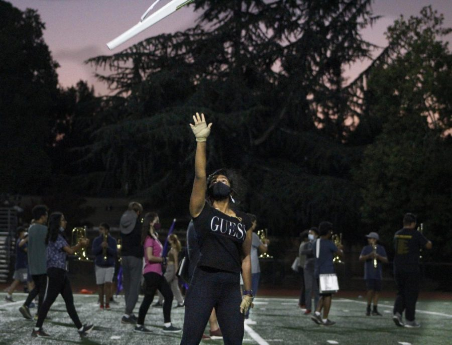 Colorguard member tossing her rifle in the air, clearly demonstrating the saying practice makes perfect.