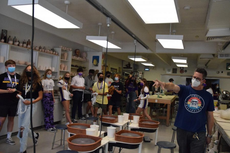 Mr. Bello, the ceramics teacher, helps lead the AV chant as the students around him engage in participation.