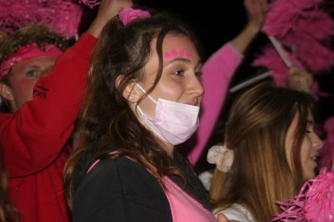 Nicole Belleville (23), all pinked-out, cheers on the varsity football team during the game