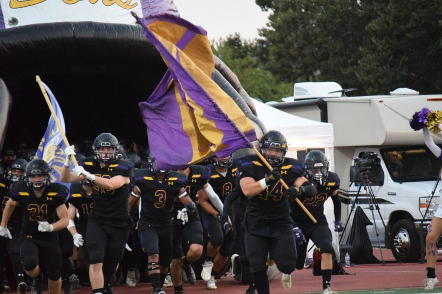 The football team runs out of the infalatable helmet, with bright flags and game day faces.